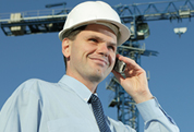 site manager in white hard hat on mobile phone